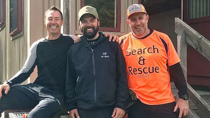 US tramper Chris Muse (centre) with rescuers Dwayne and Kris at Red Hills Hut. Muse activated a personal locator beacon after being swept away in a swollen river. Photo / Supplied