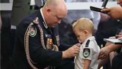 Commissioner Shane Fitzsimmons presents the medal to Geoffrey Keaton's son, Harvey. (Photo / NSW Rural Fire Service - Facebook)