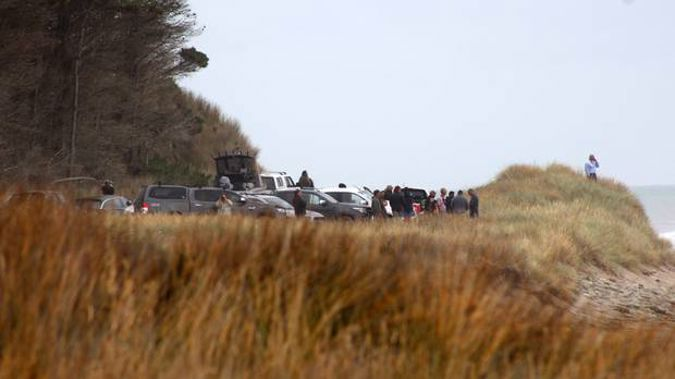 Family and friends gather on the coastline during the search for the missing father and son. (Photo / Wairarapa Times Age)