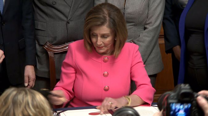ancy Pelosi signs the articles of impeachment against President Trump. (Photo / CNN)