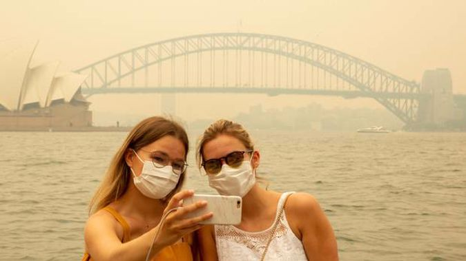 Tourists wearing masks take photos as the Sydney Opera House is enveloped in haze caused by nearby bushfires. Photo / Getty Images