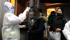 Health Officials in hazmat suits check body temperatures of passengers arriving from the city of Wuhan. Photo / AP