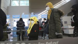 Airline passengers in South Korea wear masks while walking through the departures lounge. (Photo / AP)