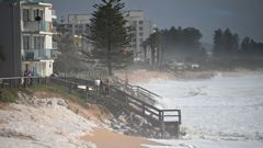 Residents watch on as sea foam brought by waves approach on beach front houses after heavy rain and storms at Collaroy in Sydney's Northern Beaches. (Photo / AP)