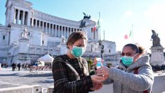 Women wearing face mask disinfect their hands in central Piazza Venezia, in Rome, Sunday, March 8. Photo / AP