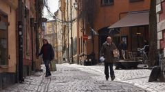 People walk down a quiet cobbled street in Stockholm. The streets are quiet but not deserted.