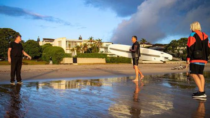 A concerned resident questions a man why he is deliberately flouting lockdown rules by surfing at Takapuna beach this morning. Another young resident, to the right, was spoken to by police yesterday.