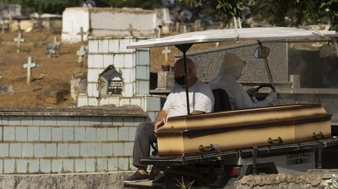 A man wearing a mask sits next the coffin of his mother as he's transported by a cemetery worker in a full protection suit to her burial site at the Nossa Senhora das Gracas cemetery in Duque de Caxias. (Photo / AP)