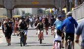 People ride and walk on a path along beach amid the coronavirus pandemic on May 15, 2020 in Huntington Beach, California. (Photo / Getty)