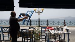 A worker places chairs at a fish restaurant ahead of its reopening in Piraeus, near Athens. (Photo / AP)