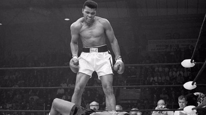 Muhammad Ali stands over Sonny Liston and taunts him to get up during their title fight in 1965. (Photo / Getty)