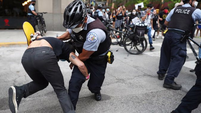 An officer takes down a protester after breaking through a police barrier during a march to bring attention to the death of George Floyd in Chicago. (Photo / AP)