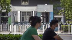 People wearing face masks to protect against the new coronavirus ride past the Australian Embassy in Beijing. Picture: Mark SchiefelbeinSource:AP