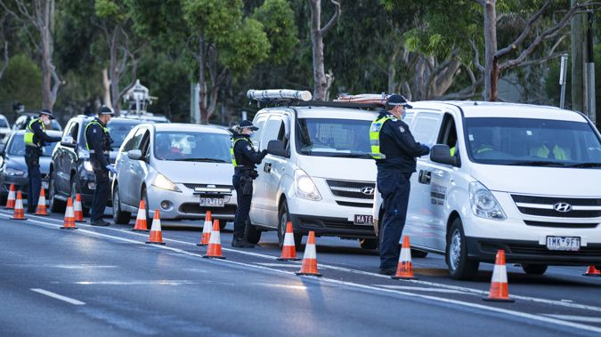 Police inspect individual drivers licenses and question drivers at a suburban roadblock site in Broadmeadows, in Melbourne,