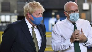 Britain's Prime Minister Boris Johnson, wearing a face mask, talks with CEO London Ambulance Service Garrett Emmerson. (Photo / AP)