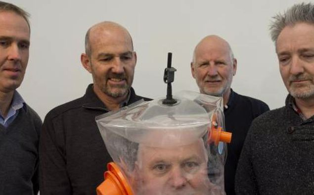 Mark Seaton, Chris Hopkins, William Early and Andrew Wallace look on as Richard Aimers tries on a ventilator hood made in Dunedin. Photo / ODT