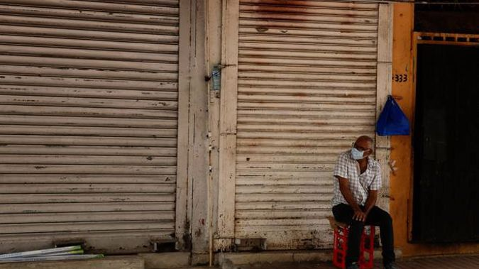 An elderly man wearing a mask to curb the spread of the new coronavirus, sits outside a closed grocery shop in downtown Panama City. (Photo / Supplied)