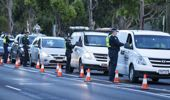 Police inspect individual drivers licenses and question drivers at a suburban roadblock site in Broadmeadows, in Melbourne.