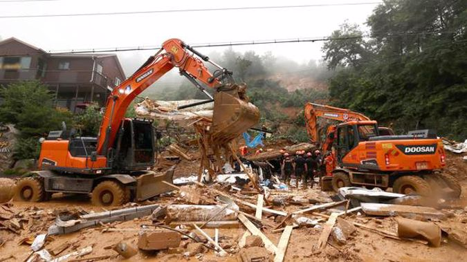Rescue workers search for survivors at a damaged house after a landslide caused by heavy rain in Gapyeong, South Korea. (Photo / AP)