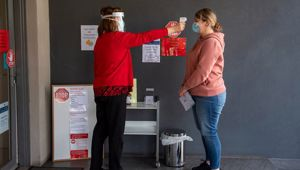 A patient has her temperature checked at a Melbourne medical clinic during lockdown due to the continuing spread of the coronavirus in Victoria. Photo / AP