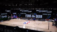 Referees huddle on an empty court at game time of a scheduled game between the Milwaukee Bucks and the Orlando Magic. (Photo / AP)