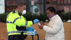Counties Manukau Police hand our face masks at the Manukau Bus Station in Monday morning. (Photo / NZ Herald)