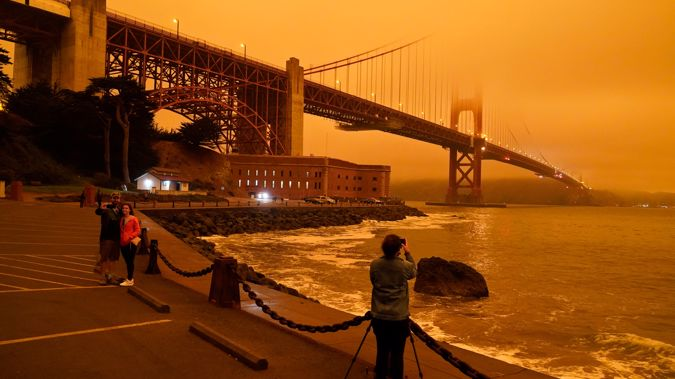 People at Fort Point in San Francisco take pictures of the Golden Gate Bridge obscured by smoke. PHOTO: Eric Risberg/AP