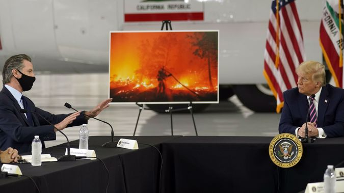 President Donald Trump listens as California Gov. Gavin Newsom speaks during a briefing at Sacramento McClellan Airport on the western wildfires. (Photo / AP)