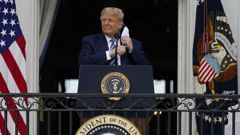 President Donald Trump removes his face mask to speak from the Blue Room Balcony of the White House to a crowd of supporters. (Photo / AP)