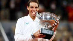 Rafael Nadal bites the winning trophy after claiming the French Open title for the 13th time  time with a straight sets victory over Novak Djokovic.