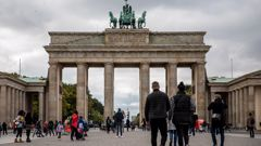 Tourists walk at the Brandenburg Gate in Berlin, as the city's businesses fight curfew orders in the courts. (Photo / Getty)