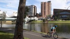 A man cycles along the Torrens River in Adelaide after the strict lockdown measures eased. (Photo / Getty)