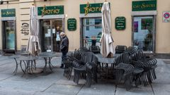 A man wearing a face mask to curb the spread of the new coronavirus walks past a closed cafe, in Turin, northern Italy on Nov. 6.