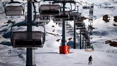 A professional athlete skis by chairlifts on Plan Maison ski run in the alpine ski resort of Breuil-Cervinia, Northwestern Italy, on November 25, 2020.