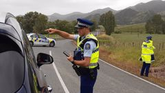 Police stop traffic after a serious shooting incident near Tangowahine on State Highway 14 in Northland. Photo / Tania Whyte