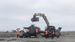The wreckage of the helicopter is removed from Kēkerengū Beach. Photo / Anna Leask