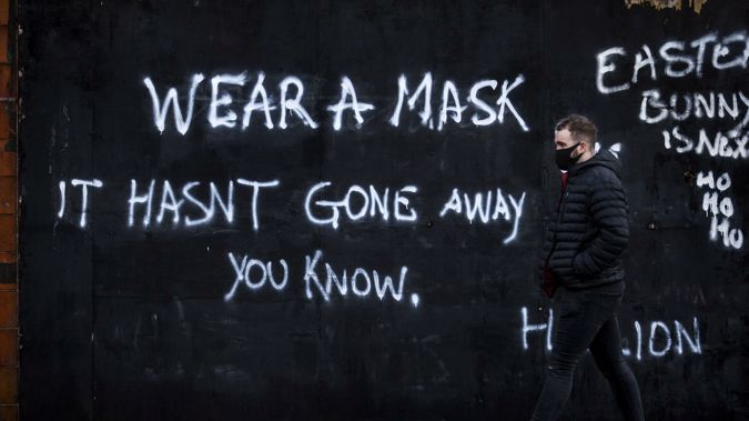 A man wearing a face covering walks past graffiti on the Lower Newtownards Road in Belfast with a message reading 'Wear a mask, it hasn't gone away you know'. (Photo / AP)