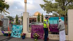 A police officer helping to attach messages to the fence at Al Noor mosque in Christchurch on the first anniversary of the terror attacks last year. Photo / Mark Mitchell