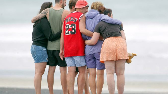People pay their respects at Bowentown Beach after a fatal shark attack. Photo / George Novak