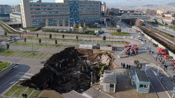 A huge sinkhole swallowed several cars and forced the evacuation of a Covid ward after opening up in the parking lot of a hospital in southern Italy. (Photo / Shutterstock via CNN)