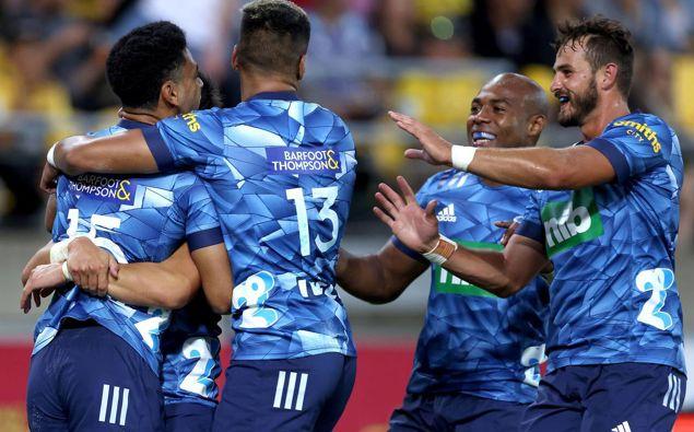 Blues' Stephen Perofeta celebrates scoring a try with teammates. Photo / Photosport