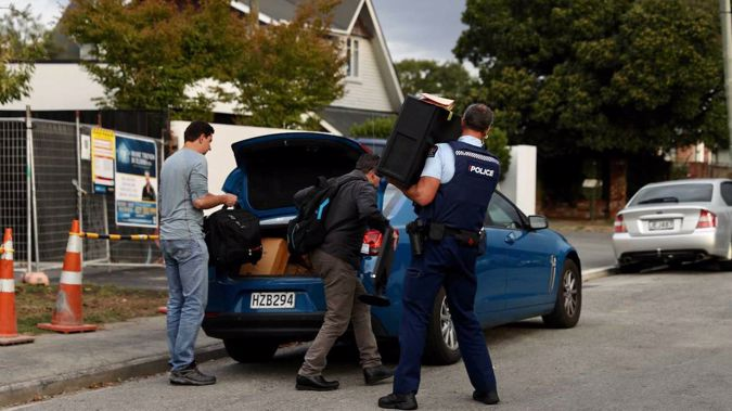 Police take computer equipment out of the house in Christchurch. Photo / George Heard