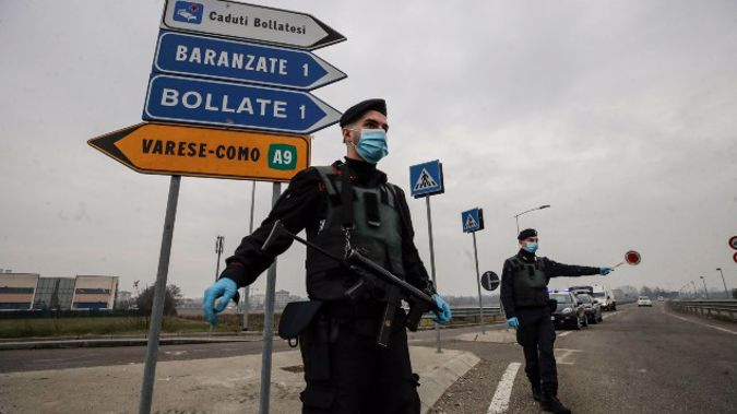 Carabinieri officers patrol one of the main access road to Bollate, in the outskirts of Milan, Italy. (Photo / AP)