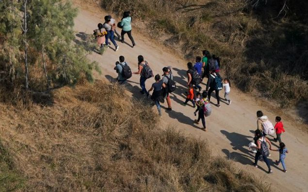 Migrants walk on a dirt road after crossing the U.S.-Mexico border, Tuesday, March 23, 2021, adnist a surge of migrants on the Southwest border has the Biden administration on the defensive. (Photo / AP)