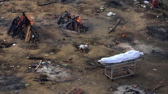 Multiple funeral pyres of those patients who died of COVID-19 disease are seen burning at a ground that has been converted into a crematorium for mass cremation of coronavirus victims, in New Delhi, India. (Photo / AP)