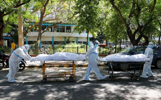 Health workers carry bodies of Covid-19 victims outside the Guru Teg Bahadur hospital in New Delhi, India. (Photo / CNN)
