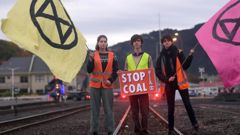 Protesters opposing the use and transport of coal block the railway tracks near the Dunedin Railway Station this morning. Photo / Stephen Jaquiery