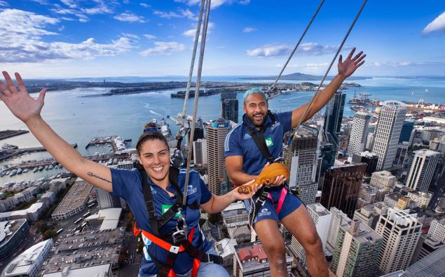 Blues Super Rugby captains Eloise Blackwell and Patrick Tuipulotu hang off the Sky Walk at the Auckland Sky Tower with the women's rugby trophy, the Waipuea Womens Rugby Taonga. (Photo / Brett Phibbs)