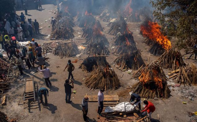 Multiple funeral pyres of victims of Covid-19 burn at a ground that has been converted into a crematorium for mass cremation in New Delhi. Photo / AP