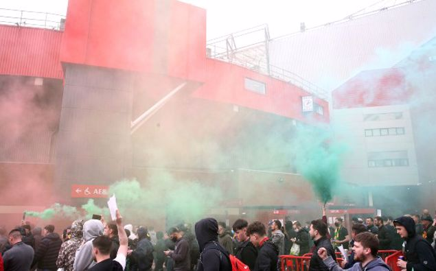 Fans make their way past barriers outside the ground as they let off flares whilst protesting against the Glazer family, owners of Manchester United, before their Premier League match against Liverpool at Old Trafford. (Photo / AP)